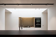 Small natural stone clad niche. Custom made kitche by Belgian interior architects iXtra.