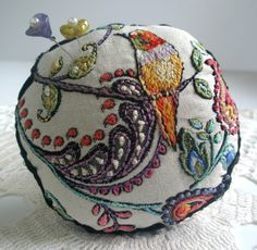 Hummingbird Pincushion. A printed fabric was enhanced with embroidery stitches. Then a picture of a hummingbird was added.