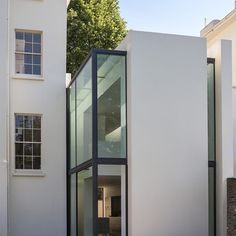 Narrow slices of glazing break up the plain white facade of this residential extension in west London helping to visually separate it from the existing house.