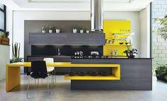Cozinha com ilha central preta e mesa embutida em madeira laqueada amarela