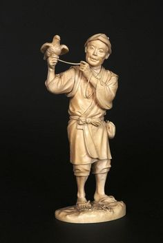 A JAPANESE IVORY OKIMONO Carved as a man holding a bird with a piece of rope attached to it, incised signature, numbered in ink 30865. 22cm