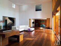 Гостиная. Квадратный проем в верхней части стены — это окно хозяйской спальни. Диван Esse, дизайнер Франческо Бинфаре, Edra. Тиковый стол и скамьи, дизайнер Жером Абель Сеген.