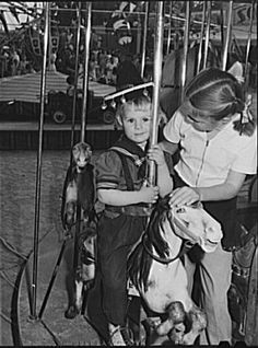 Similarly, seeing a little girl help out her younger sibling on a carousel is just as sweet of an image as it was when Russell Lee took this image at the Imperial County Fair in California back in 1942.