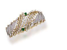 A diamond, emerald and eighteen karat gold bangle bracelet