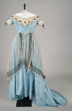 "Ca.1865 blue silk dress with net ""tunic,"" as these short overskirts were called, trimmed with ribbon. Bertha and cuffs of puffed tulle trimmed with blonde lace and black ribbon bows. Met Museum."