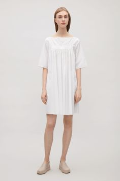 This dress is made from crisp cotton poplin with a gathered detail creating soft pleats down the front. An A-line fit and a short, tunic length, it has casual in-seam pockets, a wide neckline and neat, pinned finishes.