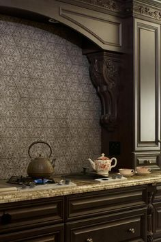 Intricate but hardworking, an embossed concrete tile backsplash in an interlocking hexagonal pattern creates a sense of formality in the kitchen when paired with traditional cabinetry.