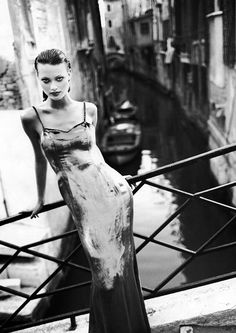 Black Lace Backless Long Gown, Black Thick Heel Pump, Colombian Stick Mask,  Hair Down And Curled. Hair Up. Standing on a Bridge.