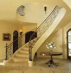 ornamental wrought iron staircase railing, stone flooring, stone stairs, iron sconces, foyer
