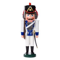 White nutcracker grenadier with blue-trimmed jacket. Traditional Erzgebirge design; hand-painted wooden nutcracker.