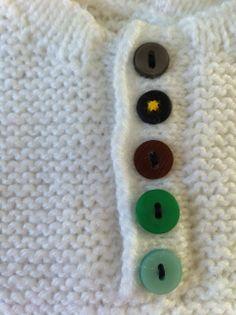 Button details on white baby knit / gekleurde knopen