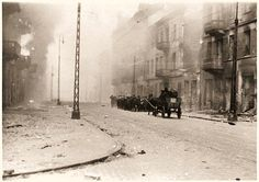 """Jews captured by the SS during the suppression of the Warsaw Ghetto Uprising are marched to the Umschlagplatz for deportation. The original German caption reads: """"How the former Jewish residential quarter looks after its destruction."""""""