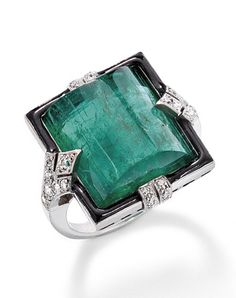 An emerald and diamond ring 15 carats, set within a black enamel border