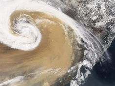 An April 2001 temperate cyclone spun counter-clockwise over China, pushing a wall of dust as it moved. The deep tan dust is not only thick enough to completely hide much of the land surface below, but it almost forms its own topography, with ridges of dust rising up below the clouds.