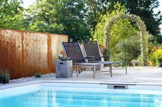 Plan Germann // Lounge-Bereich am Pool mit einem Sichtschutz aus Cortenstahl