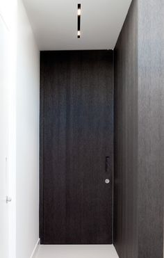 Dark wooden doors and integrated lighting, interior design by Wilfra.