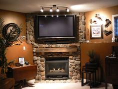 Featured, Cool Brown Wall Paint Color Background With Rustic Stoned Fireplace Mantel Plus Tv In Wall Over Wooden Shelf Plus Undulating Track Light ~ Fireplace Mantels which Works in Four Seasons that You can Set for Now