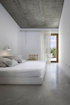 Minimalist bedroom, all white with a concrete floor