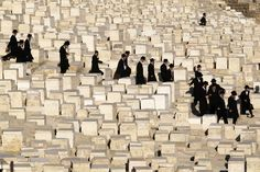 Ultra-Orthodox Jewish men walk before the funeral of Rabbi at Mount of Olives cemetery in Jerusalem