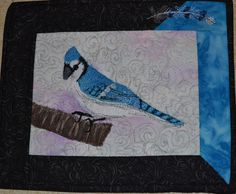 Blue Jay.  A class sample for Thread Painting.    I did use a piece of the blue fabric to establish a color background, but then all the wing and tail detail was added with layers of thread.  Contrast was a low in spots . .  a bit of ink always helps when the fabric doesn't cooperate.   Approximately 12 x 14 inches.  Note the thread painted feather in the border.