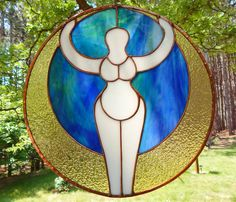 Stained Glass Mother Earth Panel. A beautiful stained glass panel of the Goddess/Earth Mother. The background is a gorgeous blue and green glass that gives the impression of Earth, and the crescent Moon that surrounds the piece is a pretty saturated yellow. Gaia, the Goddess is a soft opaque white. The solder lines are finished in a shiny copper patina and she is framed with copper as well. This is an original design created by me. I would be happy to customize color and size for you…