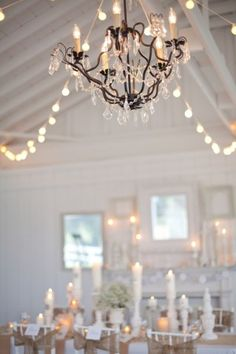 Pillar candles, string lights & a chandelier make this reception space glow! Don't forget to use the remote control on your Candle Impressions Flameless Candles to effortlessly get this look! All White Wedding, Sparkle Wedding, Crystal Wedding, Twinkle Lights, String Lights, Barn Wedding Inspiration, Wedding Ideas, Wedding Decor, Wedding Centerpieces