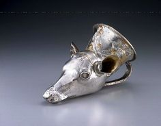 4th century B.C.E., H. 22. 5 cm.   This vessel was beaten from a single sheet of metal to form the deer head, and then the ears and handle were attached to that form. Thin hairs and eyelashes are carved on the face, and black pigment made in the niello technique of silver surface was then applied to the grooves of these incised lines. The eyelashes are the most visibly extant example of this technique. Recent research shows that the nostrils on similar vessels were also blackened through…