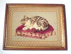 Absolutely charming needlework picture of a calico cat lying on a fancy fringed cushion.