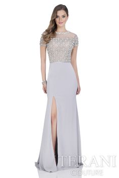 Short sleeve crepe gown with Illusion neckline and mesh bodice. This mother of the bride dress is embellished with crystals and stones arranged in a geometric motif.