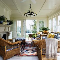 sunroom with white ceiling, wall, and flooring, rattan chair, sofa, and coffee table with mostly blue cushion and rug of The Most Proper Room to Enjoy the Best Light and Breeze of the Year