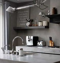 Déco 100% industrielle dans cette cuisine grise avec du béton ciré sur carrelage couleur taupe sur le mur de crédence.