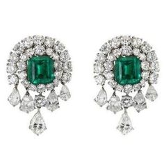 VAN CLEEF & ARPELS • Each of these magnificent Van Cleef & Arpels earrings features a large, center emerald-cut emerald surrounded by round-cut diamonds, with dangling pear-shaped diamonds adding drama to the 18K white gold setting. Accompanied by certificates stating that the emeralds are Colombian, and untreated. Circa 1990s by tamara