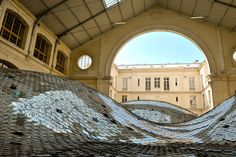 waste landscape, by artist Elise Morin and achitect Clémence Eliard. 65,000 CD's were collected, sorted, and hand-sewn to fill the Centquatre at the Halle d'Aubervilliers in Paris. stunning.