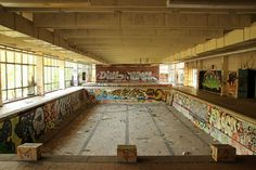 """Einen Lost Place entdecken – Alte Schwimmhalle Pankow. Hier wurde schon lange nicht mehr durchs Becken gekrault. Die ehemalige Freizeit- und Sportstätte ist zum Abenteuerspielplatz geworden. Schon beim """"Durch-die-Absperrung-quetschen"""" fängt der Nervenkitzel an. Das Schwimmbecken im Innern ist zur Kunstbühne für Graffiti-Sprayer geworden."""