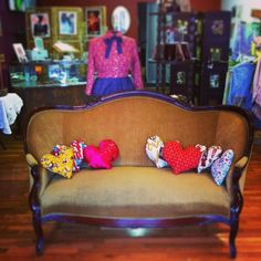 Handmade heart pillows in funky fabrics on the welcoming *Love* seat for Valentine's Day at the Scarlett Garnet storefront at 2619 Cherokee Street in south St. Louis.  scarlettgarnet.com etsy.com/shop/scarlettgarnet #boutiquedisplay #boutique