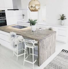 this faded wood island brings personality into a white, minimalist design.