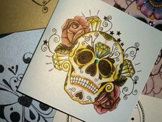 Tattoo design style luxury handmade card, greeting card, blank card, birthday card, tattoo flash illustration of a sugar skull, dias de los muertos, decorated with re roses and emeralds.