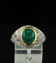 Antique Deco emerald and diamond ring in elegant domed design    The front panel is richly set by old cut diamonds in adorable pattern of foliate design  surrounding the centre large cabochon cut emerald set into rub over frame    Carved details edging the borders    All crafted of solid 18 Kt gold in white and yellow colours - marked