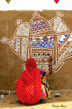 INDIA - Woman doing decorative painting of her home for the Pushkar Camel Fair - Rajesthan