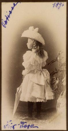 Princesa Tatiana Constantinovna, em 1896. Ela está em pé virada para a esquerda, de costas para a câmera. Ela está usando um vestido de renda de cor clara, com uma grande laço na parte de trás, um chapéu decorado com penas e calças escuras. Ela está segurando um guarda-chuva e há um grande vaso de plantas para a direita. A fotografia é anotado com seu nome e a data.