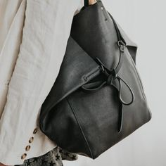 Tie me up or let me loose. This luxuriously soft leather tote will fit all your day to day essentials. You have the option of structured tie together closing, or open casual hold all practicality. FEATURES Internal zip pocket Key clip Limited edition key ring and dust bag Leather ties MATERIALS 100% leather exterior Co Soft Leather, Leather Bag, Key Rings, Bucket Bag, Dust Bag, Ties, Essentials, Exterior, Pocket