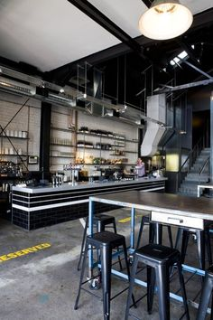 Bar with industrial furniture, concrete floor, black subway tile, exposed ducts