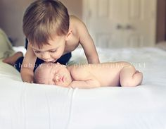 sibling kissing newborn, or pic with baby like this and siblings behind with hands on faces, laying down, elbows on bed