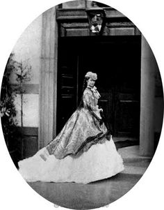 Sissi wears a huge skirt that almost forms a bustle in this photo, one of a series of her wearing the same hat, mantle, and dress.