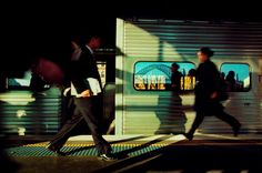 Trent Parke. AUSTRALIA. Sydney. Rush hour in the morning as a woman runs to catch the train at Circular Quay train station.The Sydney Harbour bridge is reflected in one of the passenger windows. 2000