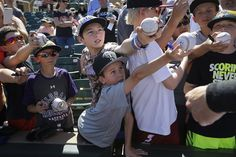"""Brody Martin bottom center and Brayden Miracle top center try to get their balls signed by Colorado Rockies' Charlie Blackmon before the Rockies' spring training baseball game with the San Francisco Giants in Scottsdale Ariz. #APPhoto by @jaechongpix  MLB's spring training is underway and for the next three days we will be sharing coverage by AP staff photographer based in Los Angeles Jae C. Hong.  We asked Jae about his experience covering this year's events and this is what he said """"In a…"""