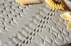 A simple and brilliant idea to be realized at school with clay slabs: colored tiles imprinted with different shapes of pasta.Farfalle, penne, fusilli or spaghetti become interesting tools to creat…