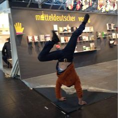 "We designed this year's tradeshow stand for Mitteldeutscher Verlag with the topic ""Hands"". Because our clients and visitors liked the concept, our Partner Helmut did a handstand at the hand-stand. Previous Year, Handstand, Trade Show, Leather Pants, Concept, Marketing, Germany, Pencil, Creative"