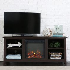 """Create a warm, entertaining space in any room of your home with this TV stand with fireplace. Crafted from high-grade MDF with a laminate finish to accommodate most flat panel TVs up to 60"""". Features adjustable shelving and a cable management system."""