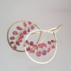 .........raspberry meets cherry...... Made to order with a two week turnaround. Slight differences because they are handmade. 20 gauge 14k gold filled wire has been hand forged into hoop style earrings. Slightly teardrop in shape and framing vines of pink sapphires, in varying shades (rose, pink grapefruit) that are rather unusual and beautiful. At either end of vines sit dark pink tourmaline. Finished length is 1 7/8. Width, at widest, is just a shot over 1. Thank you, Tracey More ...
